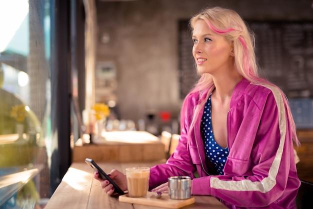 Gelukkig jonge mooie blonde vrouw denken tijdens het gebruik van telefoon in de coffeeshop