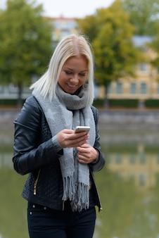 Gelukkig jonge mooie blonde vrouw met behulp van mobiele telefoon in het park langs de rivier