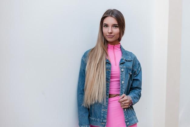 Gelukkig jonge mooie blonde vrouw met een schattige glimlach in een modieuze denim jurk in een glamoureuze roze top in roze korte broek is buiten in de buurt van een vintage muur op een zomerdag. mooi vrolijk meisje.