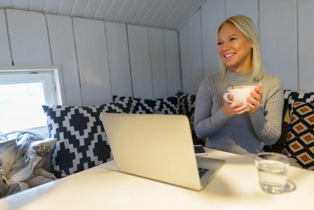 Gelukkig jonge mooie blonde vrouw thuis koffie drinken met laptop en glas water