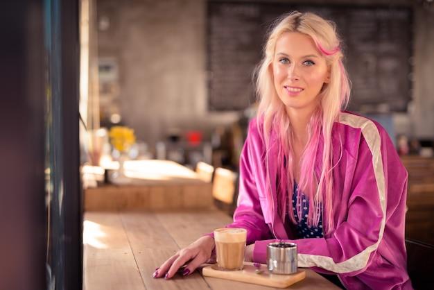 Gelukkig jonge mooie blonde vrouw zitten en ontspannen in de coffeeshop