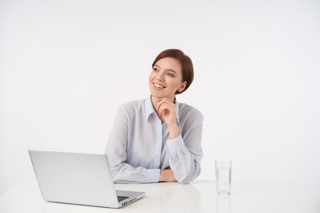 Gelukkig jonge mooie brunette vrouw met casual kapsel werken in moderne kantoren met laptop, glimlachend aangenaam terwijl opzij kijken en kin met opgeheven hand vasthouden, geïsoleerd op wit