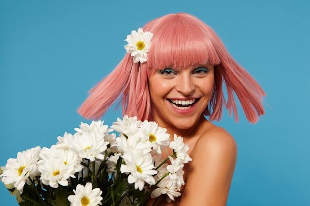 Gelukkig jonge mooie groenogige vrouw vrolijk haar korte roze haren zwaaien en positief kijken naar camera met brede glimlach, armvol bloemen vasthoudend terwijl poseren op blauwe achtergrond