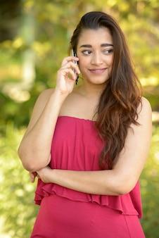 Gelukkig jonge mooie indiase vrouw praten aan de telefoon in het park