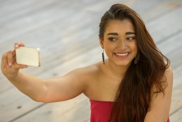 Gelukkig jonge mooie indiase vrouw selfie te nemen zittend op de houten vloer