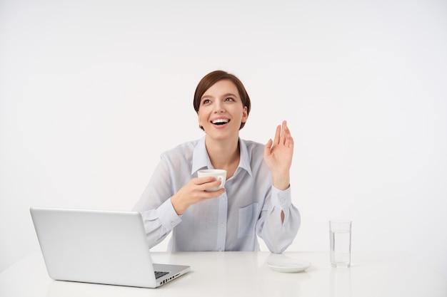 Gelukkig jonge mooie kortharige vrouw met natuurlijke make-up glimlachend vreugdevol terwijl het drinken van koffie en het verhogen van haar handpalm in hallo gebaar, geïsoleerd op wit