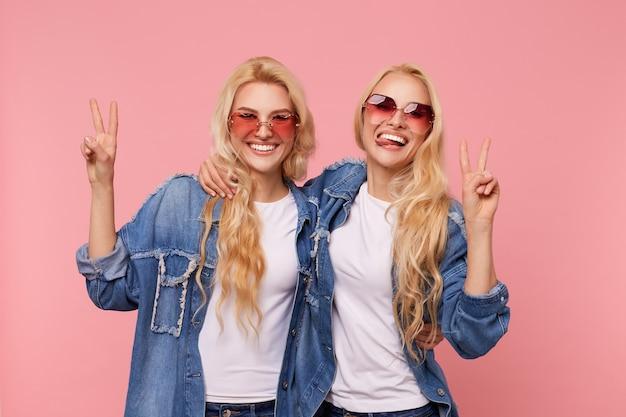 Gelukkig jonge mooie langharige blonde dames in zonnebril en vrijetijdskleding verhogen handen met overwinningstekens en vrolijk kijken naar camera, geïsoleerd op roze achtergrond