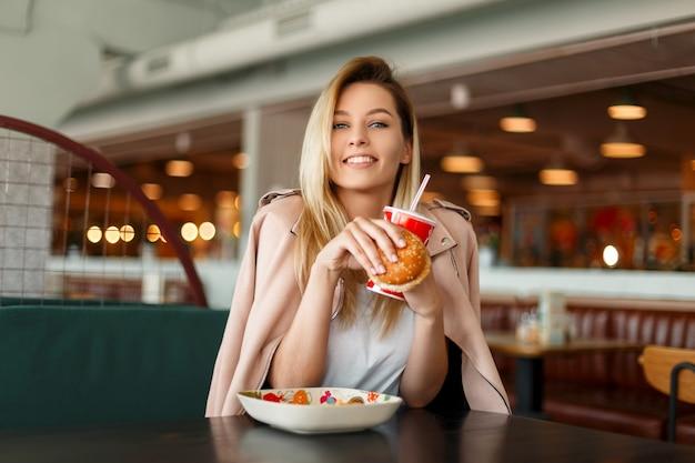 Gelukkig jonge mooie vrouw in roze jasje met fastfood, hamburger en cola zitten in café