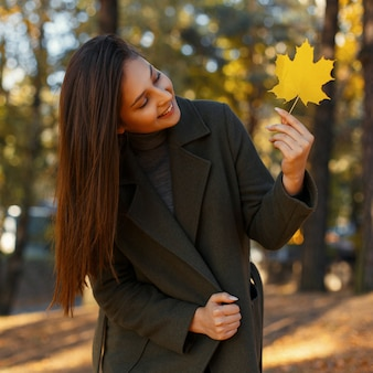 Gelukkig jonge mooie vrouw met een glimlach in een modieuze jas met een gele herfstblad wandelingen in het park op een zonnige dag