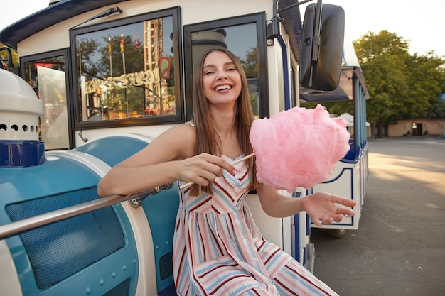 Gelukkig jonge mooie vrouw met lang bruin haar zitten in de buurt van stoomtrein auto in pretpark, zomerjurk met riemen dragen en stok met roze suikerspin vasthouden, lachen en kijken