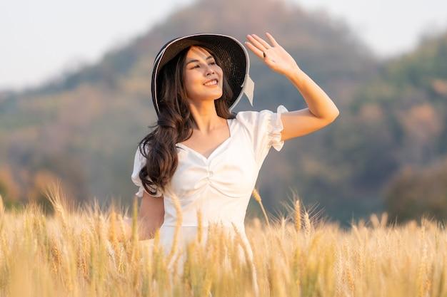 Gelukkig jonge mooie vrouw met zwarte hoed en witte jurk die haar hand omhoog houdt om te blokkeren voor de zon die op haar gezicht schijnt tijdens het wandelen in het gouden gerstveld op een late namiddag