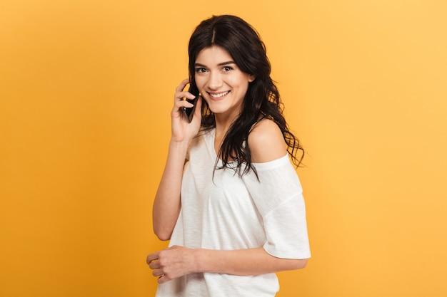 Gelukkig jonge mooie vrouw praten via de mobiele telefoon.