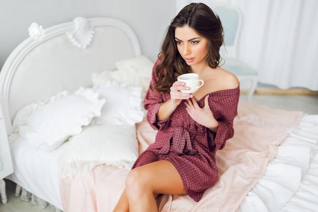 Gelukkig jonge mooie vrouw thee drinken en lachen, genieten van nieuwe dag, zittend op haar stijlvolle bed, met kussens