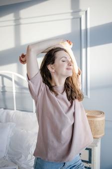Gelukkig jonge mooie vrouw trekt haar handen omhoog, staande naast het bed in haar slaapkamer thuis