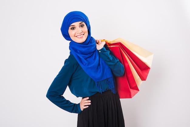 Gelukkig jonge moslimvrouw met boodschappentas op witte achtergrond.