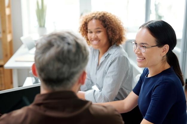 Gelukkig jonge multiculturele zakenvrouwen luisteren naar hun baas of collega tijdens het bespreken van ideeën op werkvergadering