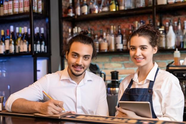 Gelukkig jonge ober notities maken in kladblok terwijl zijn mooie collega met touchpad in de buurt staat en allebei naar je kijken