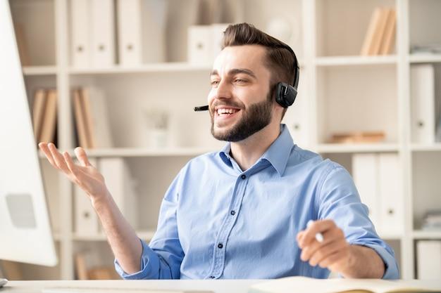 Gelukkig jonge officemanager met hoofdtelefoon iets uit te leggen aan een van de klanten tijdens het communiceren via videochat