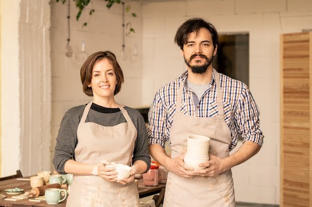 Gelukkig jonge professionele pottenbakkers met aardewerk staan in hun atelier