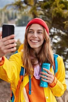 Gelukkig jonge reiziger glimlacht gelukkig, doet selfie met mobiele telefoon, gekleed in gele anorak, houdt thermoskan met thee, heeft recreatie in prachtig bos