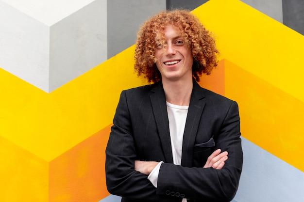 Gelukkig jonge roodharige man in stijlvolle jas armen glimlachend en kijken terwijl je in de buurt van muur met kleurrijke geometrische versiering op straat in de stad