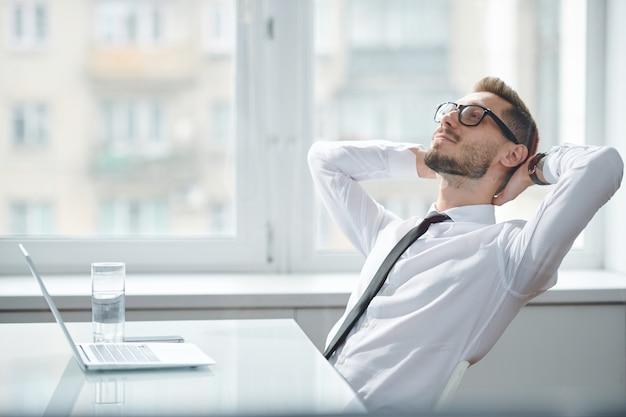 Gelukkig jonge rustgevende kantoormedewerker in stropdas en wit overhemd zittend door bureau tegen raam en dagdromen bij pauze