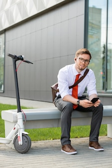 Gelukkig jonge rustgevende zakenman met smartphone zittend op de bank tegen buitenkant van modern gebouw buitenshuis