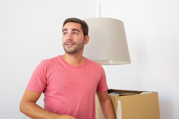 Gelukkig jonge spaanse man dingen uitpakken in zijn nieuwe flat, staande in de buurt van kartonnen dozen, wegkijken