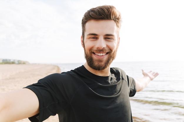 Gelukkig jonge sportman met koptelefoon een selfie te nemen