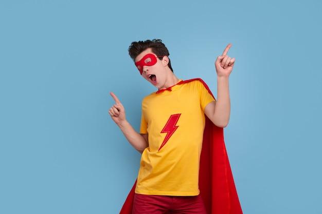 Gelukkig jonge superheld in kleurrijk kostuum gebaren en dansen met geopende mond tegen blauwe achtergrond