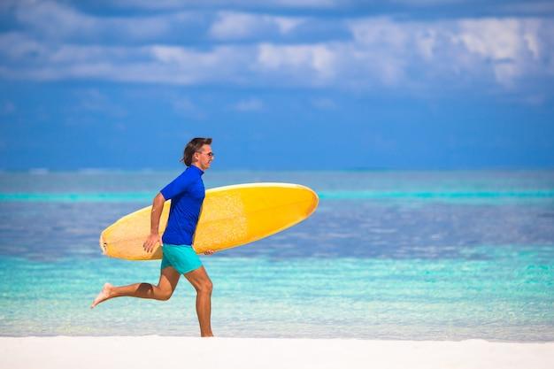 Gelukkig jonge surf man loopt op het strand met een surfplank