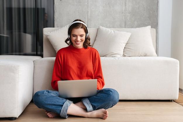 Gelukkig jonge terloops geklede vrouw zittend op een vloer thuis, studeren met laptop