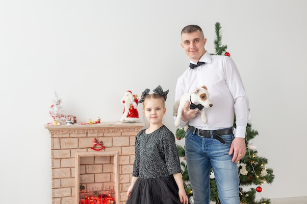 Gelukkig jonge vader en zijn dochter thuis met kerstboom.