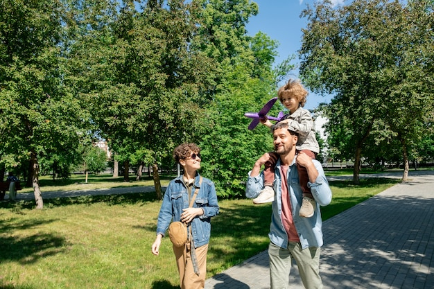 Gelukkig jonge vader met schattige zoontje met speelgoed vliegtuig op zijn nek en praten met vrolijke vrouw tijdens wandeling in openbaar park
