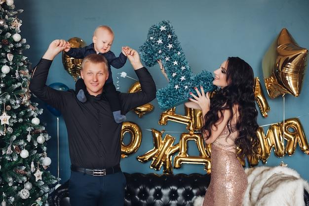 Gelukkig jonge vader schattige baby op zijn schouders te houden tijdens het vieren van verjaardag met mooie moeder op kerstavond. vakantie concept