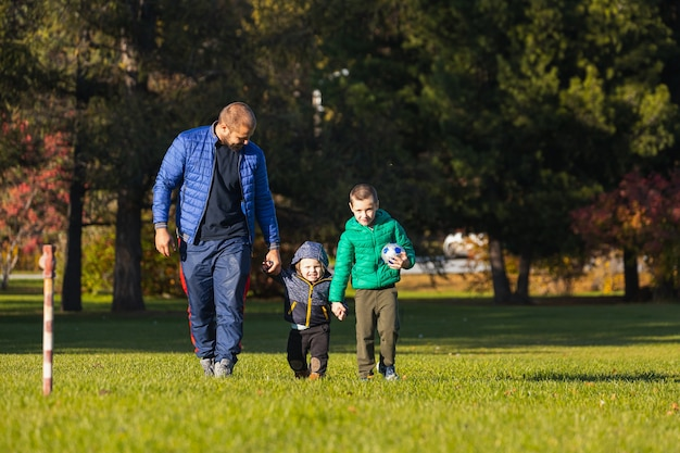 Gelukkig jonge vader speelt met zijn baby en zoon in een park op een groen gazon
