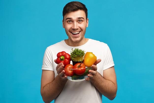 Gelukkig jonge vegetariër poseren bij blauwe muur met glazen kom met verse biologische groenten die hij zelf verbouwde op zijn boerderij, opgewonden gelaatsuitdrukking hebben, mond wijd openhoudend
