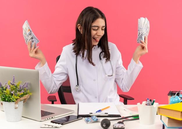 Gelukkig jonge vrouw arts in witte jas met een stethoscoop om haar nek met contant geld glimlachend vrolijk zittend aan tafel met laptop over roze muur
