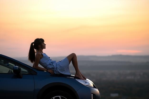 Gelukkig jonge vrouw bestuurder in blauwe jurk genieten van warme zomeravond haar auto kap opleggen. reizen en vakantie concept.