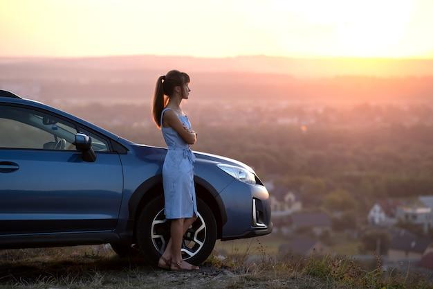 Gelukkig jonge vrouw bestuurder in blauwe jurk genieten van warme zomeravond staande naast haar auto. reizen en vakantie concept.
