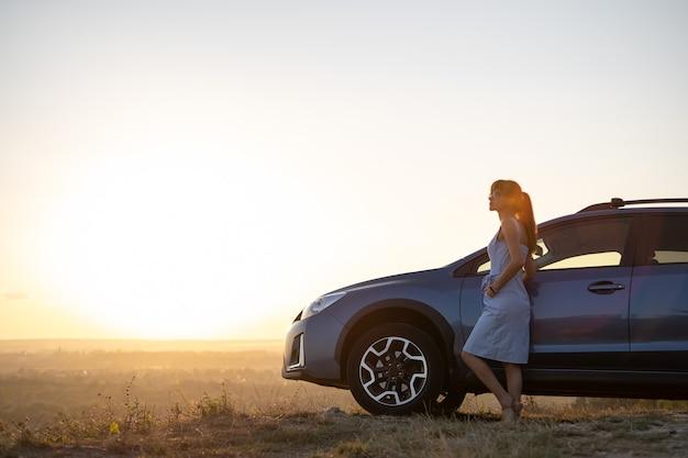 Gelukkig jonge vrouw bestuurder in blauwe jurk leunend op haar auto genieten van warme zomerdag. reizen en vakantie concept.