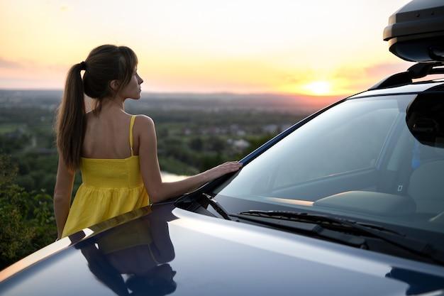 Gelukkig jonge vrouw bestuurder in gele jurk leunend op haar auto genieten van warme zomerdag. reizen en vakantie concept.