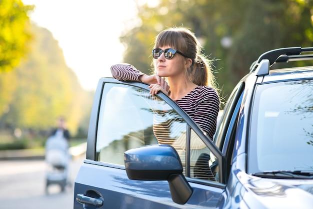 Gelukkig jonge vrouw chauffeur genieten van warme zomerdag staande naast haar auto op een stadsstraat. reizen en vakantie concept.