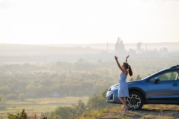 Gelukkig jonge vrouw chauffeur met uitgestrekte handen genieten van warme zomeravond naast haar auto. reizen en vakantie concept.