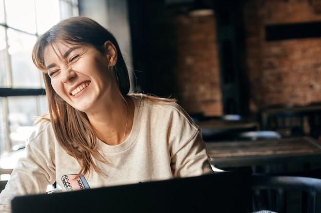 Gelukkig jonge vrouw communiceert online met behulp van computer.