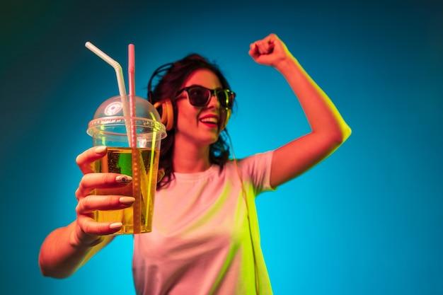 Gelukkig jonge vrouw dansen en glimlachen in koptelefoon over trendy blauwe neon studio