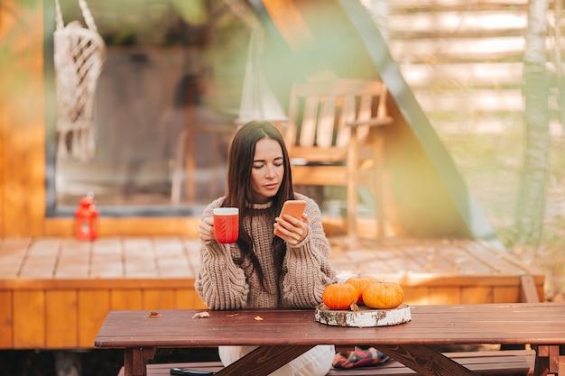 Gelukkig jonge vrouw drinken koffie zittend aan de houten tafel buitenshuis