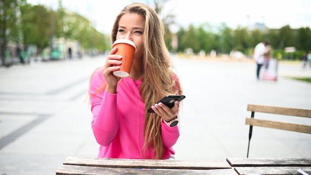 Gelukkig jonge vrouw een kopje koffie buiten drinken tijdens het gebruik van haar smartphone