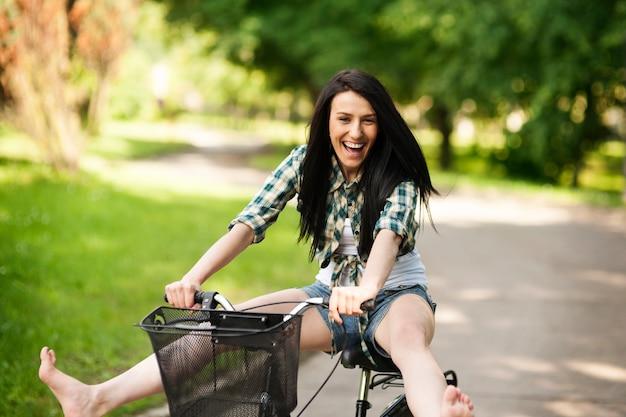 Gelukkig jonge vrouw fietsen door het park