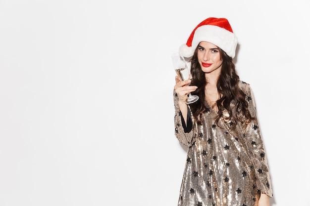 Gelukkig jonge vrouw, gekleed in glanzende jurk en kerstmuts vieren nieuwjaar geïsoleerd over wit, met glas champagne